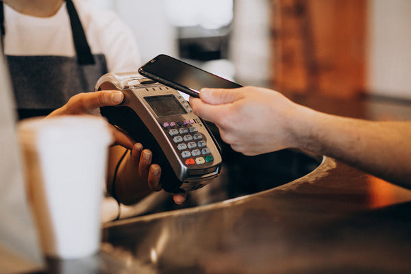 paying for coffee with black mobile phone