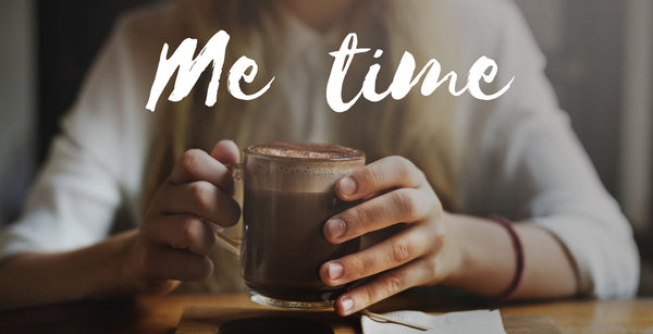 woman holding hot chocolate with white cursive writing above reading 'me time'