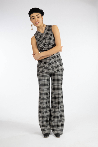 Model wearing Tanya Taylor's white and black plaid jumpsuit, coupled with large hoop earing and a black beret.