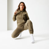 Female model with brown hair sitting wearing Frosted Olive Ukiyo Hoodie and Frosted Olive Ukiyo Ultimate Joggers