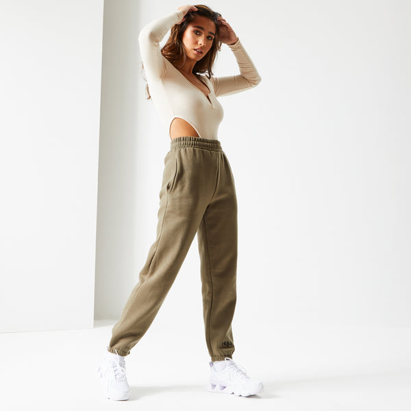 Female model with brown hair standing wearing Frosted Olive Ukiyo Ultimate Joggers
