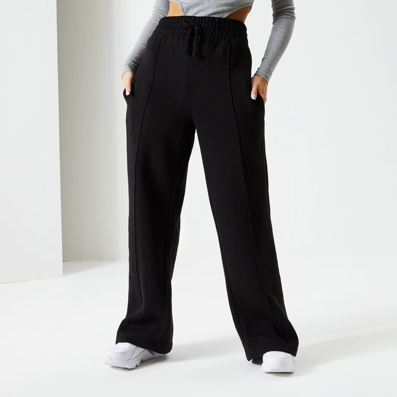 Female model standing wearing Jet Black Pin Tuck Wide Leg Ukiyo Joggers