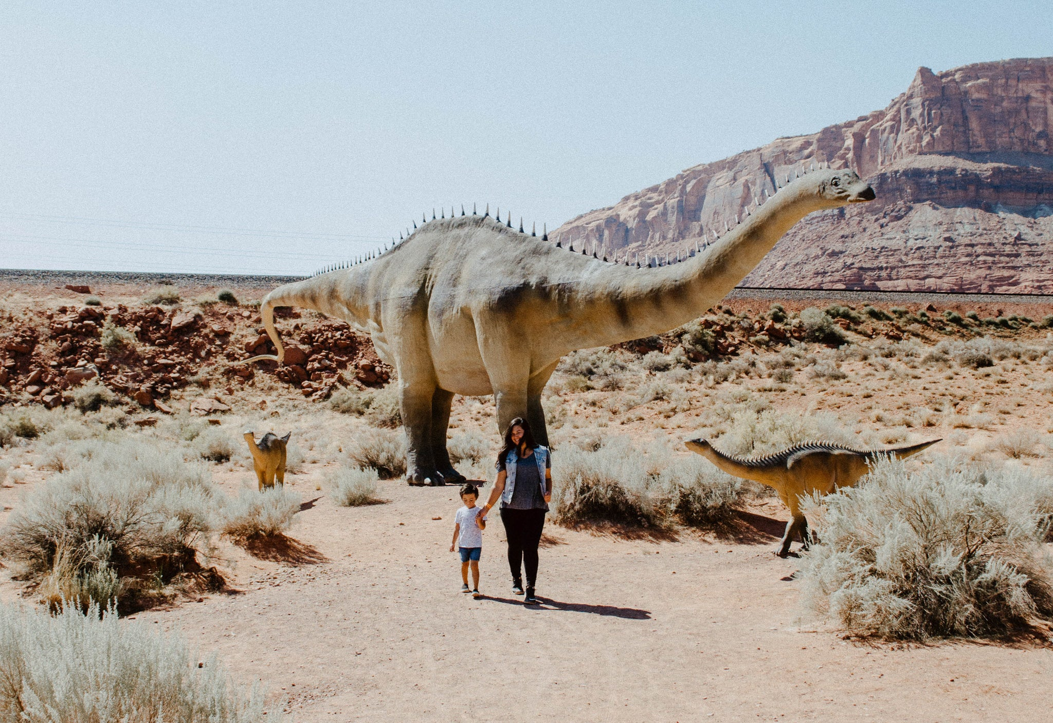 woman and child walking in front of dinosaur statues