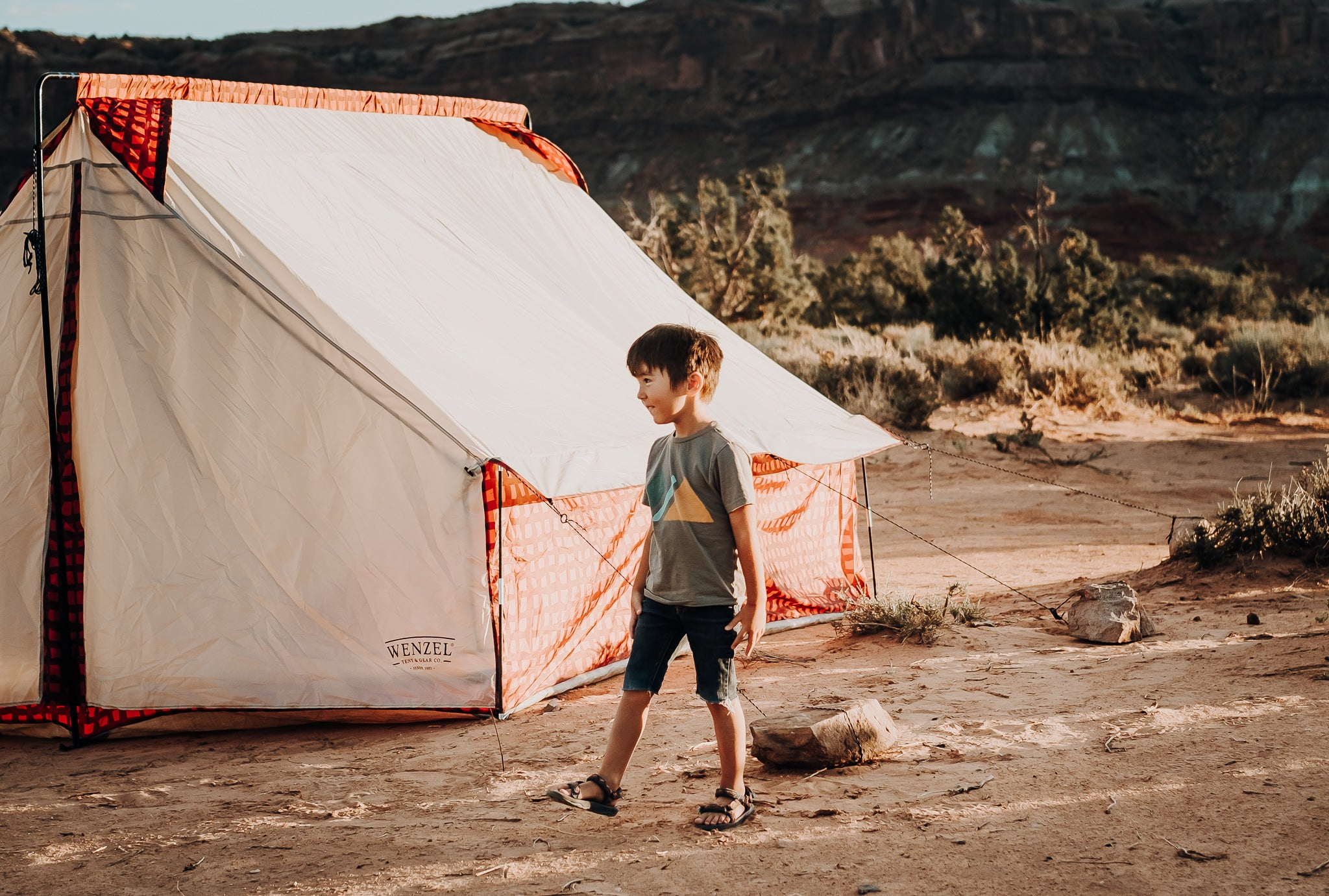 Kid standing next to a tent in the desert