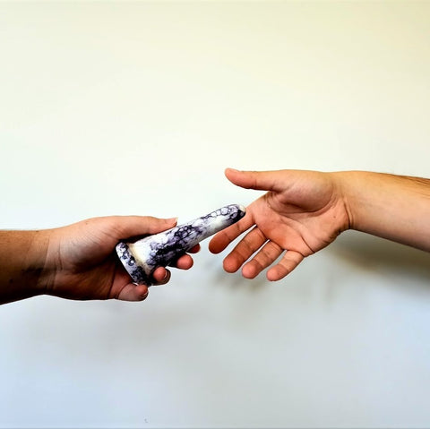 A hand holds a 4 inch ceramic dildo in a purple bubble pattern, while another hand reaches for it, against a white background
