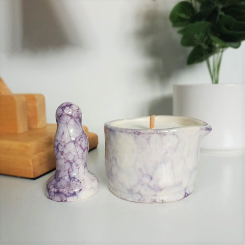 A small ceramic butt plug and a matching ceramic massage candle in a dark purple bubble pattern stand on a white bedside table. A wooden lamp and a dark green plant in a white pot are visible in the background.