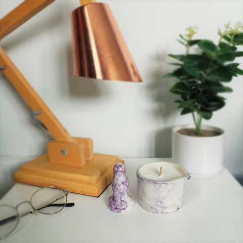 A small ceramic butt plug and a matching ceramic massage candle in a dark purple bubble pattern stand on a white bedside table. A pair of wire-rimmed glasses lay to the left, and a wooden lamp with a copper shade and a dark green plant in a white pot are visible in the background.