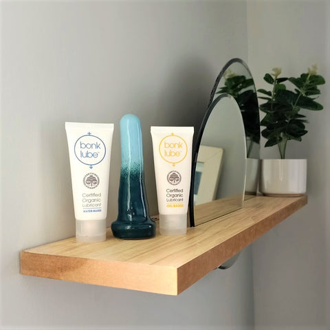 Two tubes of Bonk organic lubricant stand either side of a 4 inch classic ceramic dildo in a dark green to light blue gradient pattern. The items stand at the end of a wooden shelf on a white wall, with circular mirrors inserted into the shelf. A pot plant stands at the other end of the shelf.