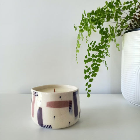 A ceramic massage candle in a purple pattern stands on a white table against a white wall. A bright green fern flows from a pot on the right.