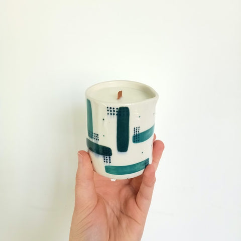 A massage candle in a green and teal pattern is held by a hand in front of a white wall. The candle is tilted forward so you can see the wooden wick in the centre of the candle.