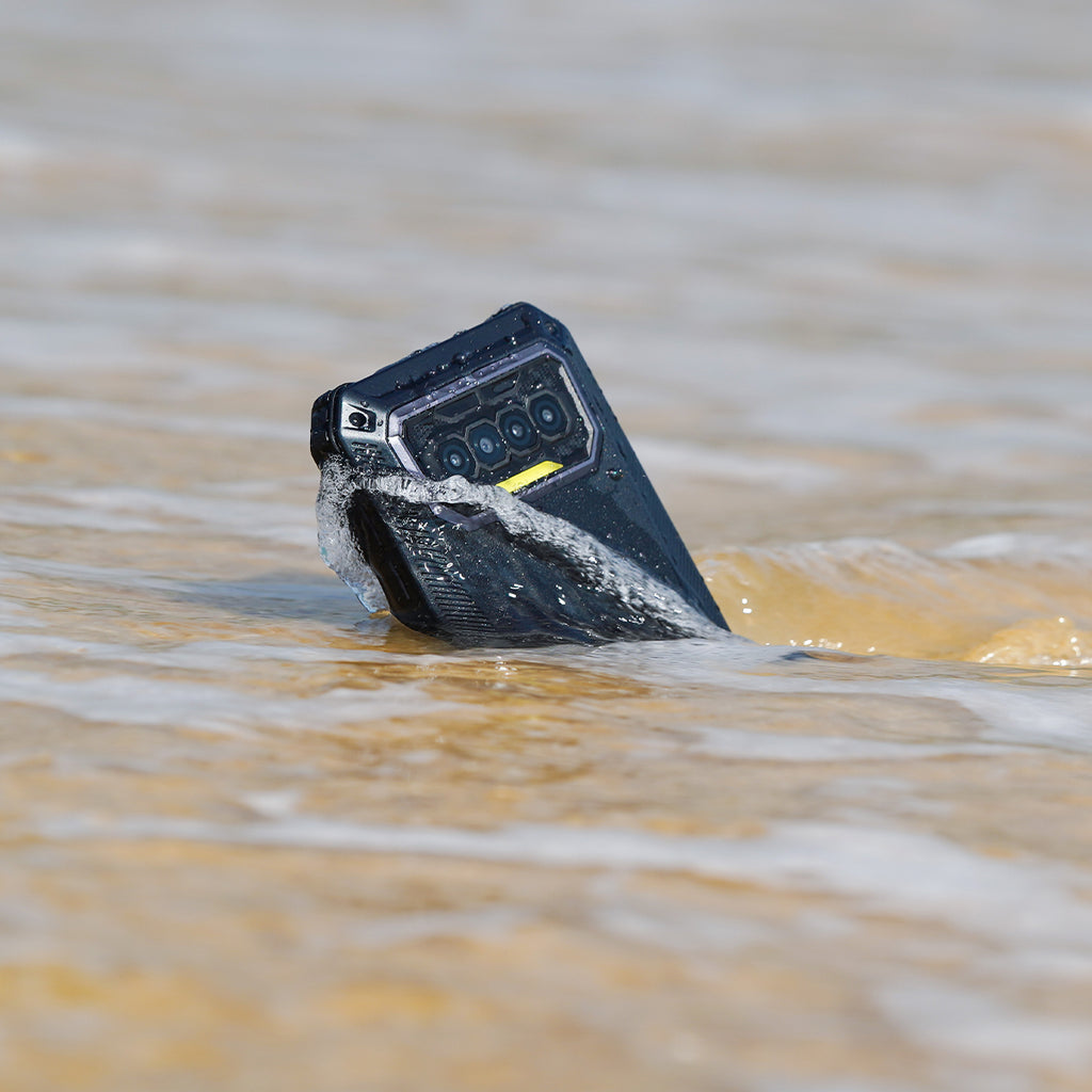 F150's B2021 displays its IP68 and IP69k water resistant abilities on show. The device is partially buried on the beach as the sea water rushes by