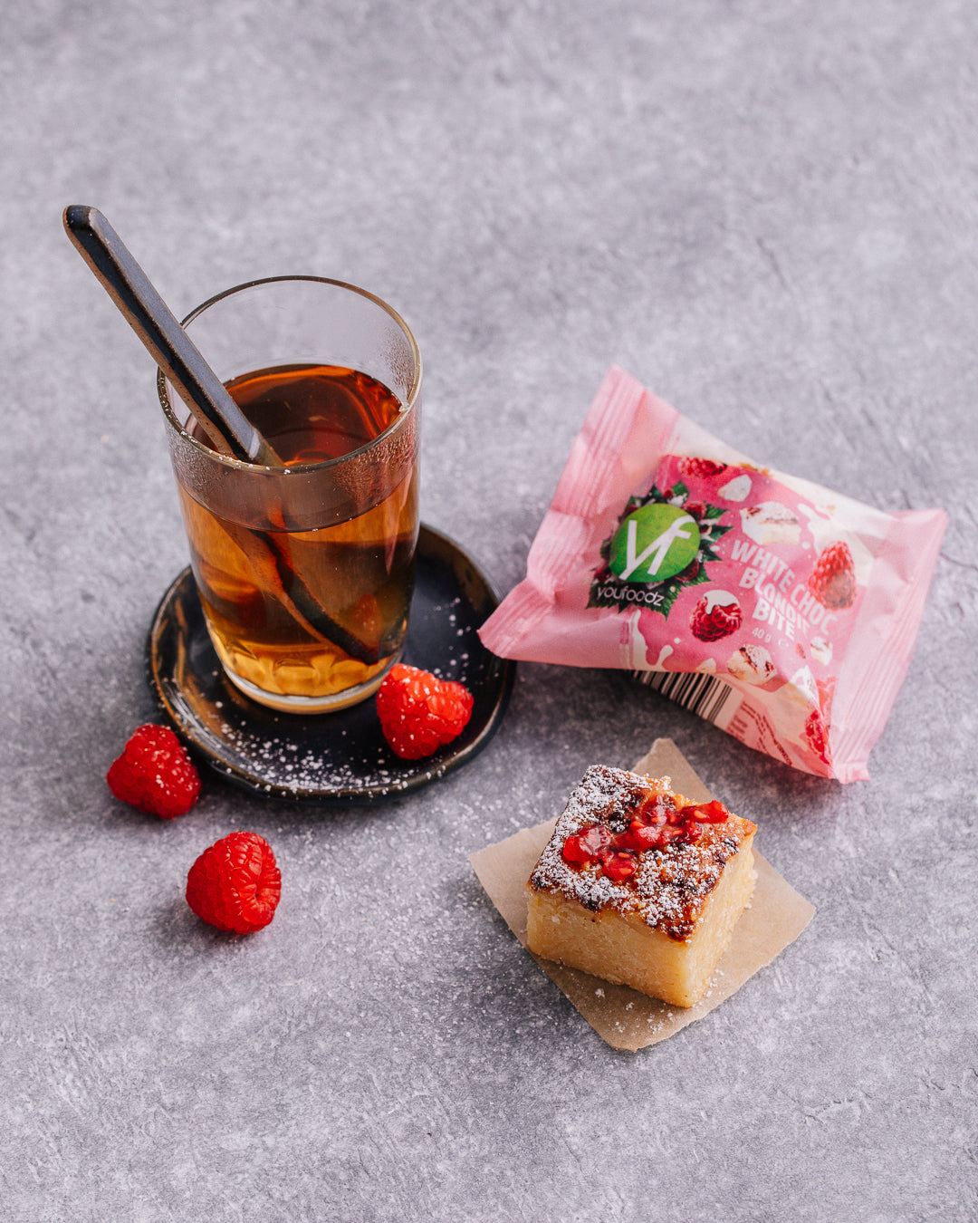 White Choc Blondie Bite with a clear cup of herbal tea