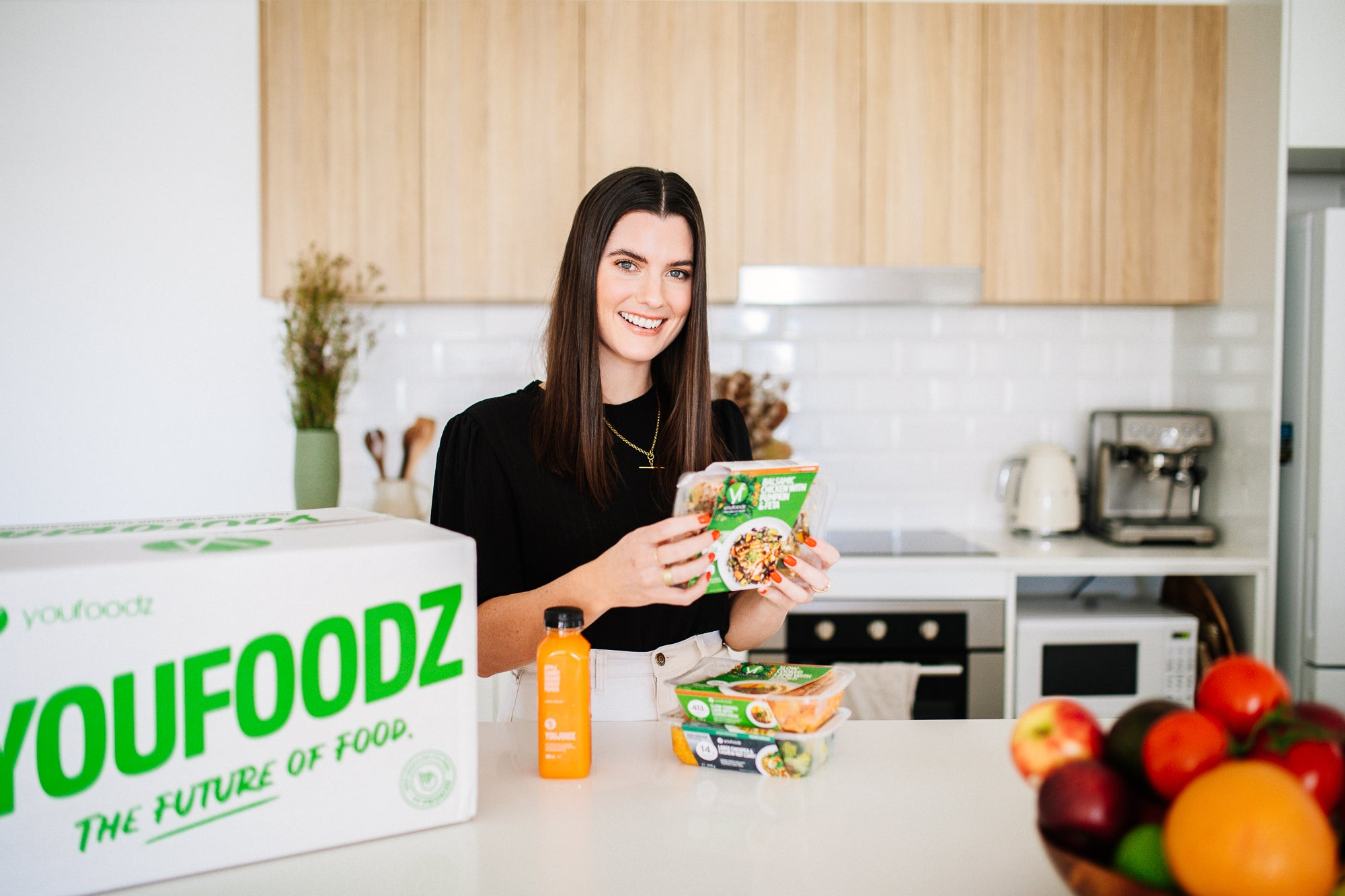 Tess standing in her kitchen holding a Youfoodz meal. On the bench is also a Youfoodz box
