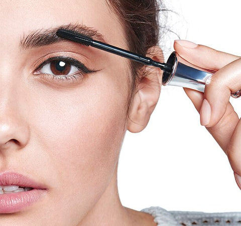 A photo of a person applying The Simple Brow to their eyebrow with the applicator wand