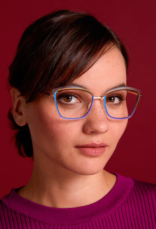 Beautiful woman in brown hair is wearing a pair of Mad in Italy glasses in titanium and nylon. The new eyeglasses are a cat-eye shiny purple.