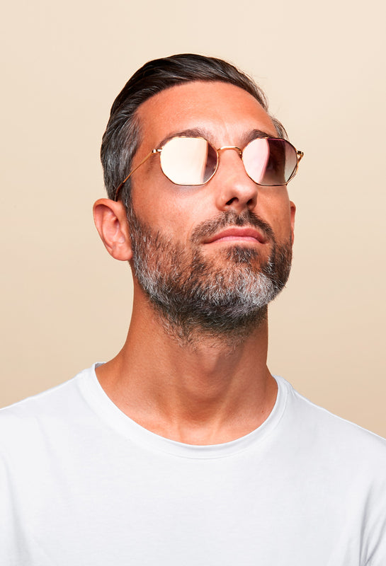 Man with beard is looking at the sky and is wearing metal sunglasses frames and a white t-shirt.