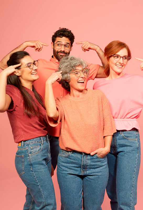 "4 people are smiling and are doing with the fingers the Italian gesture for ""crazy"". They are wearing Mad in Italy fashion metal and plastic frames. The colours of the pictures are pink tones."