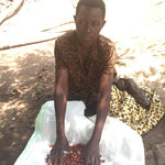 Female coffee farmer sits with white towel holding red coffee cherries