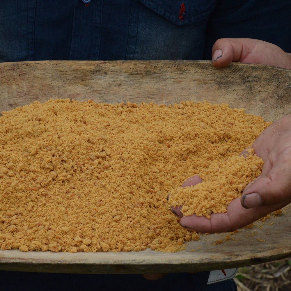 Closeup hand lifts cane sugar from wooden dish