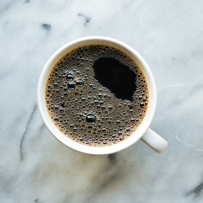 White coffee mug with black coffee on marble counter