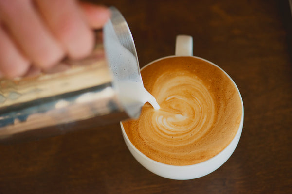 Pouring steamed milk into latte on wooden counter