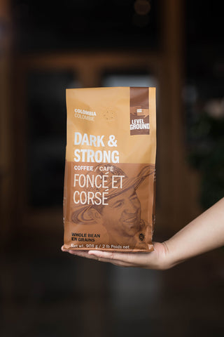 Outstretched hand holding 2lb Colombia dark roast coffee bean package
