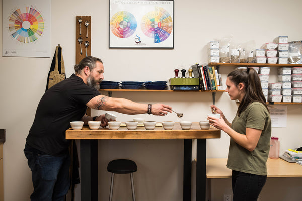 Two people stand at wooden table, cupping coffee
