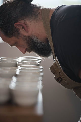 Man smelling coffee in small, white cupping mugs covering table
