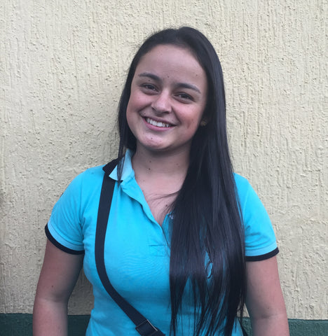 Young girl in blue shirt smiling for camera