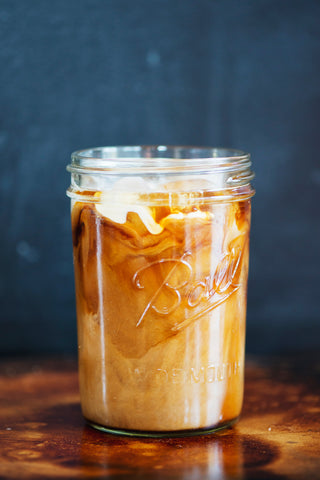Mason jar with coffee and cream mixing together