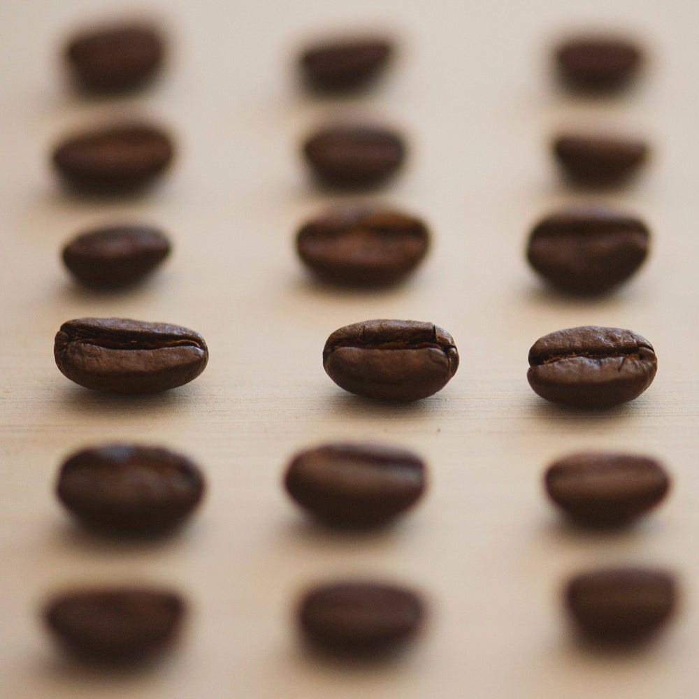 Roasted coffee beans on white surface