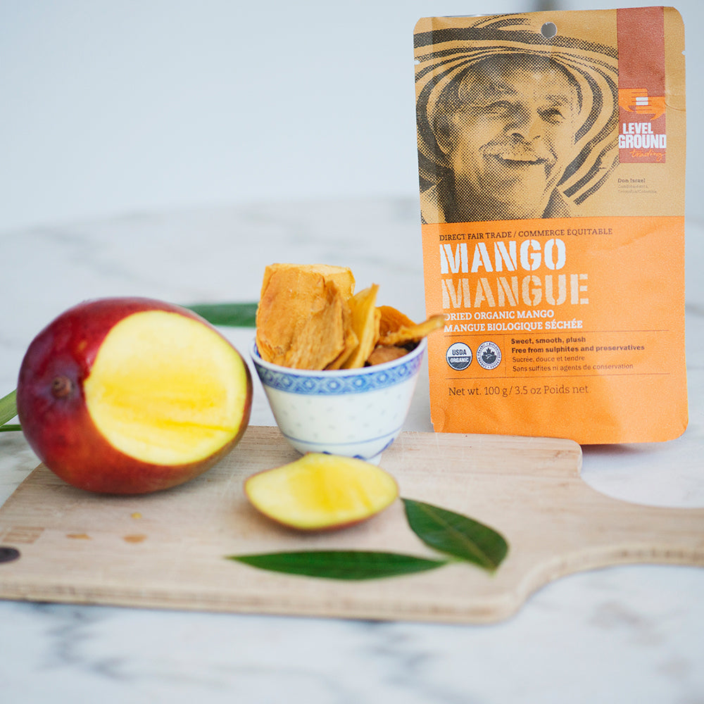 Organic dried mango, 100 gram package, fresh mango on cutting board