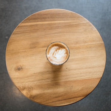 Latte in glass on circular wooden table