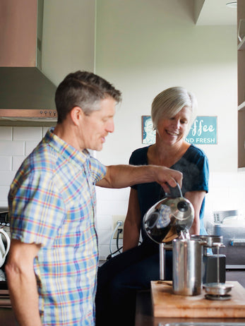 Man brewing french press coffee, lady sitting on kitchen counter watching