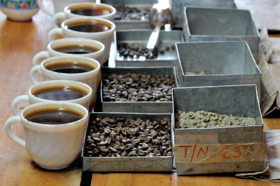Six white mugs with black coffee, silver trays with coffee beans