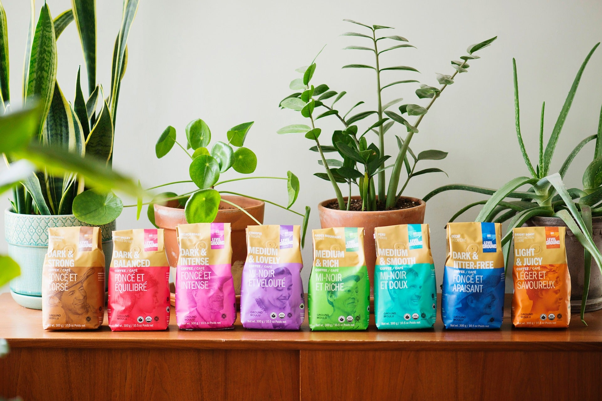 300g coffee packages in row on table, potted plants behind