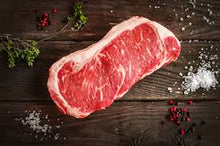 Load image into Gallery viewer, This 16oz Prime Boneless NY Strip is a thing of beauty. The marbling makes this steak ultra flavorful.  Of all the beef produced in the U.S., only 2% is certified prime grade by the USDA.  Our USDA prime beef comes from the very finest corn-fed cattle the Midwest has to offer. The Crooked Butcher personally know each and every producer that we work with to ensure that you only get the highest of quality meat with the most mouth watering flavor.