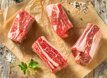 Load image into Gallery viewer, Beef Short Ribs are cut from the lower portion of the rib cage and have a nice thick layer of fat-laced meat on top of the bone. These Short ribs are cut into individual size bones and are perfect for slow cooking such as braising or on the grill or smoker. The Crooked Butcher
