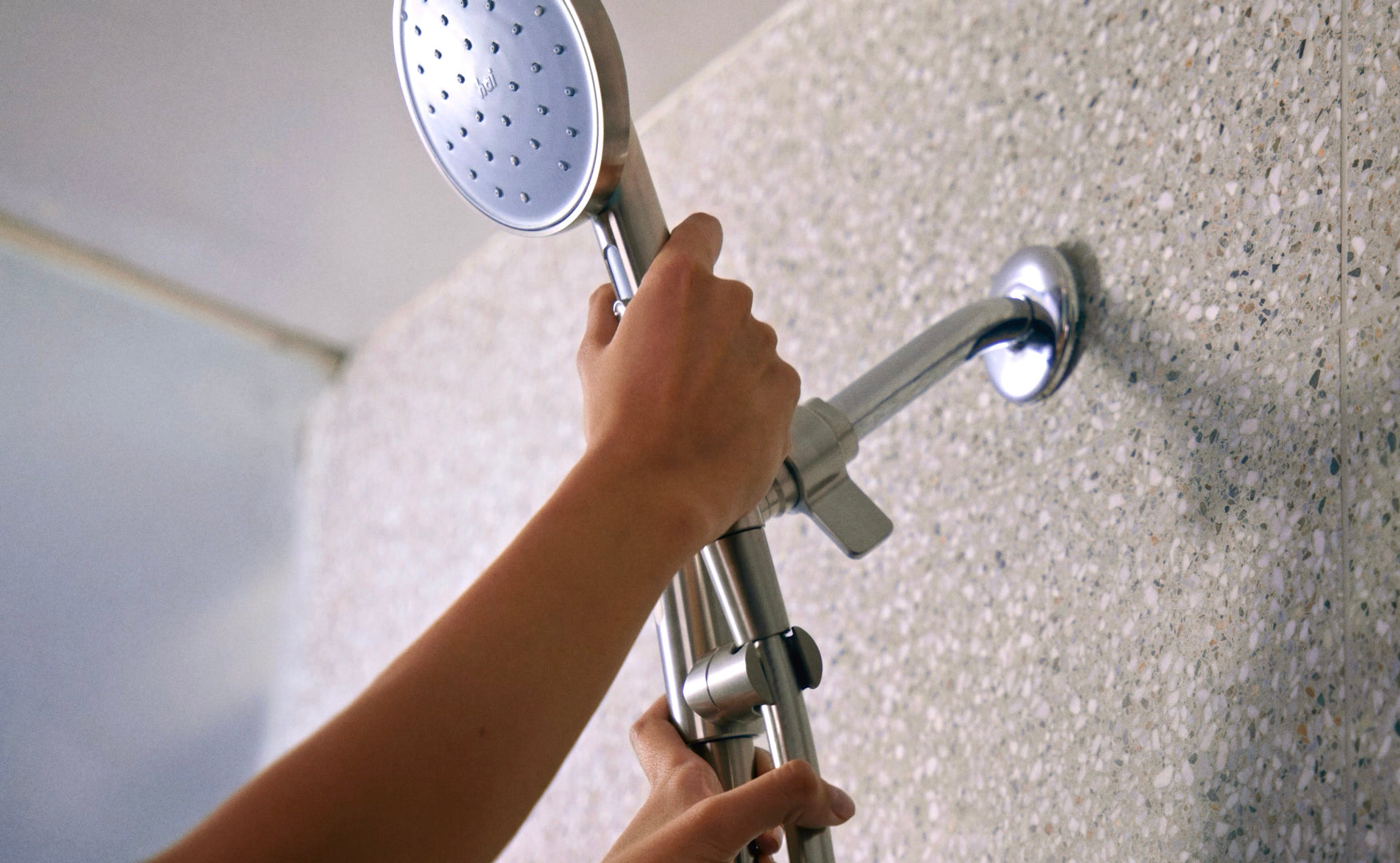 Hand putting hai showerhead handle into it's docking place