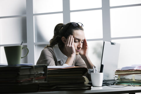 Which Type of Kava Will Work for Your Stress and Anxiousness? Woman sitting at a desk, stressed out from work.