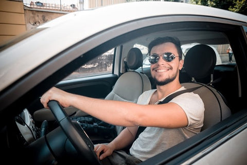 Can I Mix Kava and Alcohol? Young man smiling while looking out his rolled down car window.