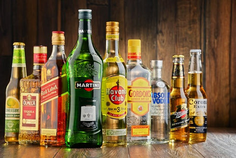 How Does Alcohol Work? Many liquor bottles all full with different brands of alcohol.