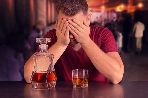 Negative side effects of alcohol. Man sitting at a bar after having drank too much alcohol.