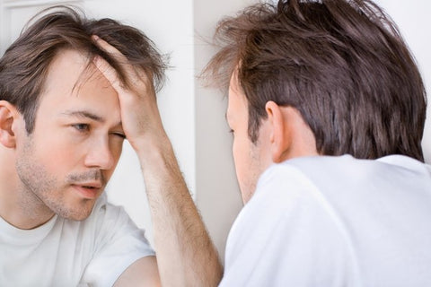 What About Hangovers? Man looking at himself in the mirror after drinking too much alcohol.