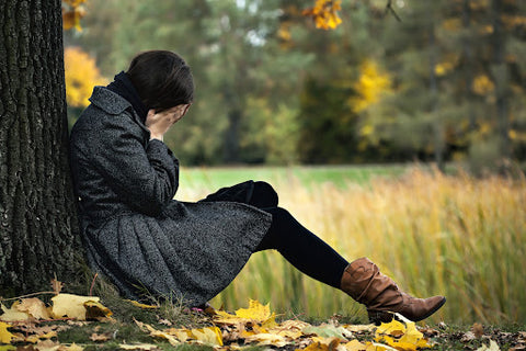 Using Kava to Relieve Anxiety. Woman sitting under a tree with her head in her hands, anxious and depressed.