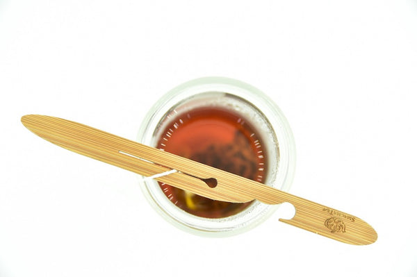 A bamboo tool is laid across the top of a glass cup. The string of a sachet tea bag is threaded through a slot in the middle of the tool.