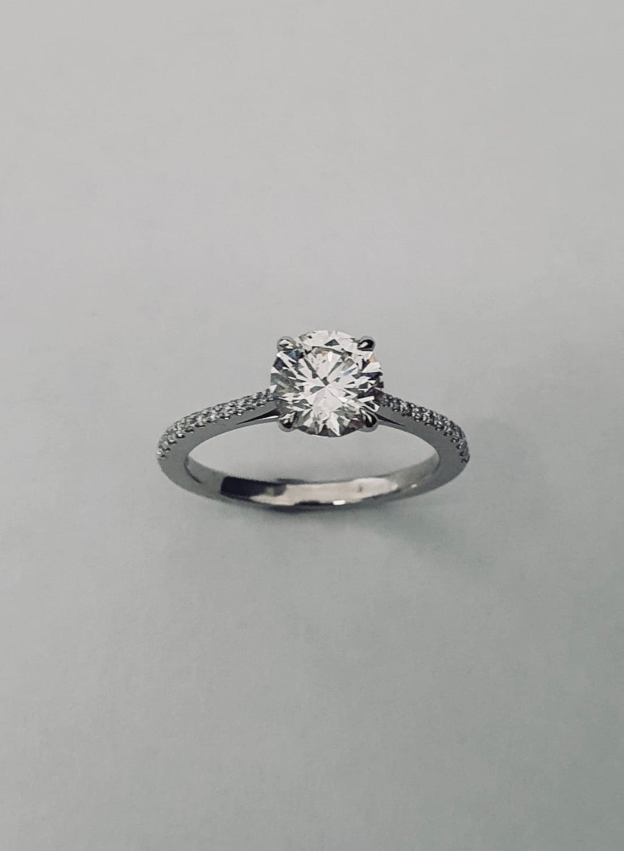 An elegant Platinum Solitaire Engagement Ring see with a Round Brilliant Cut Diamond and Diamond set shoulders