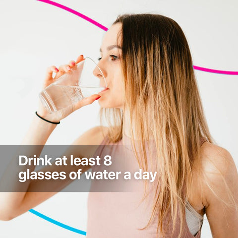 A brunette woman drinking a glass of plain water side view