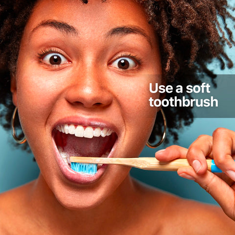 brown skin woman brushing her teeth with a toothbrush