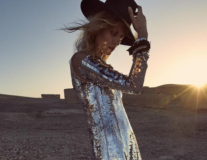 model in silver sequins dress and hat in desert